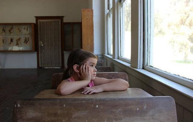 Girl in school classroom looking out the window