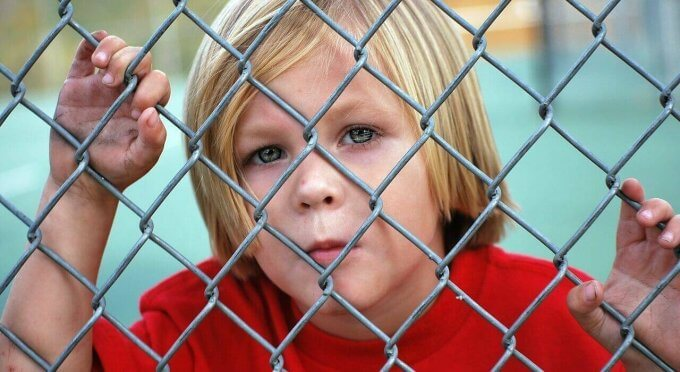 boy looking through chain link fence