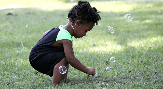 Little girl in grass with bubbles