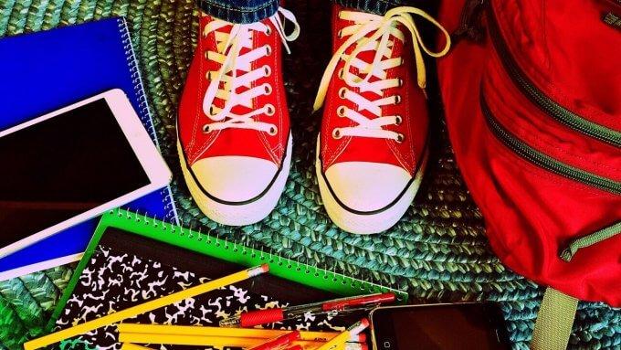 school supplies, backpack, feet in sneekers