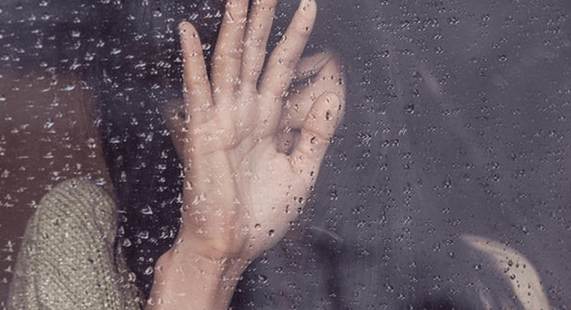 Cognitive Behavioural Therapy CBT - woman with hand covering face pressed against a rain splattered window