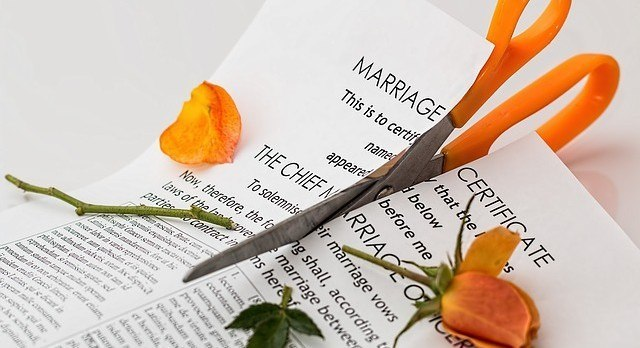 Scissors cutting up a Marriage Certificate and a rose