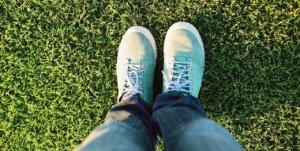 feet in sneakers in grass