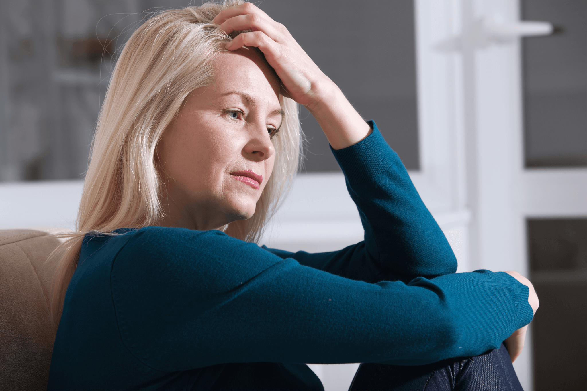 A blond, mature, white woman in a blue pullover sitting with her left hand on her forehead looking depressed.